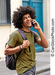 smiling young man walking outside with bag and talking on mobile phone