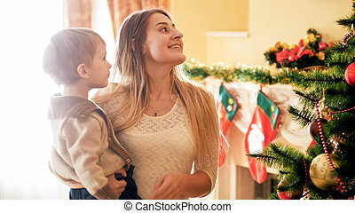 Portrait of smiling young mother with her little boy looking on Christmas tree at living room