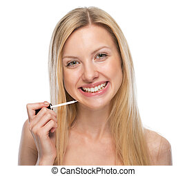 Portrait of smiling young woman applying lip gloss