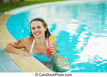 Portrait of smiling young woman at pool with cocktail