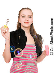 Portrait of smiling young woman blow bubbles