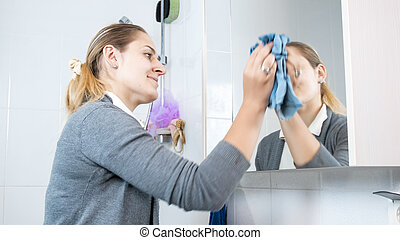 Portrait of smiling young woman cleaning stains from mirror...