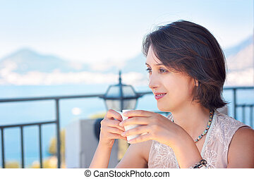 Young Woman Drinking Coffee at Cafe Terrace