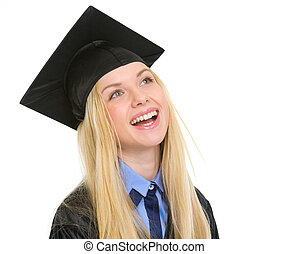 Portrait of smiling young woman in graduation gown looking on copy space