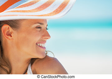 Portrait of smiling young woman in hat on beach looking on copy space