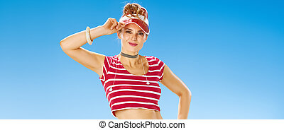 Portrait of smiling young woman in red sun visor on seacoast...