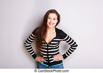 smiling young woman in striped sweater against gray wall