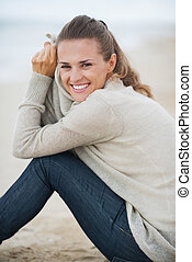 Portrait of smiling young woman in sweater sitting on lonely beach