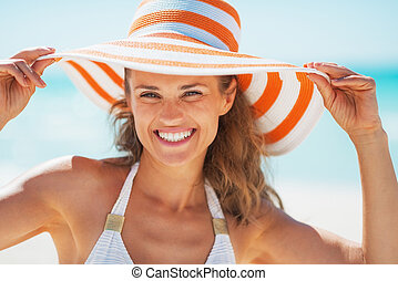 Portrait of smiling young woman in swimsuit and beach hat