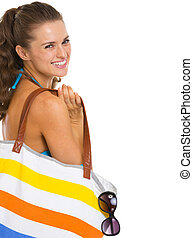 Portrait of smiling young woman in swimsuit with beach bag
