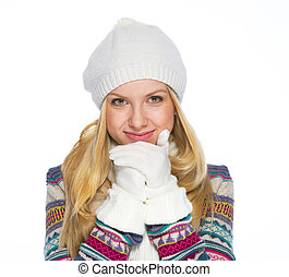 Portrait of smiling young woman in winter clothes warming hands
