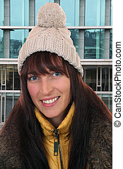 Portrait of smiling young woman in winter in town