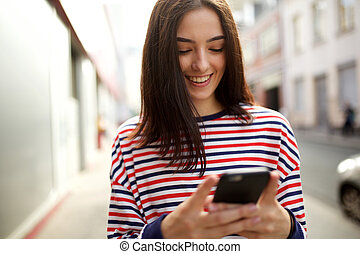 smiling young woman looking at cellphone in city