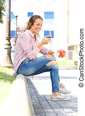 smiling young woman looking at mobile phone in the park