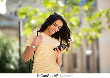 smiling young woman looking at mobile phone outside in city