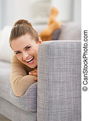 Portrait of smiling young woman looking out from sofa