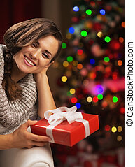 Portrait of smiling young woman near christmas tree holding present box