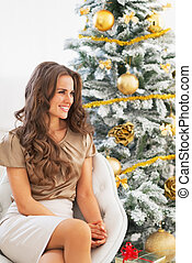 Portrait of smiling young woman near christmas tree looking on copy space