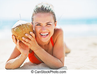 Portrait of smiling young woman on beach holding coconut