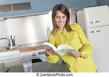 Portrait of smiling young woman reading book in kitchen at home