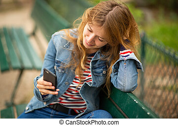 smiling young woman relaxing on park bench looking at mobile phone