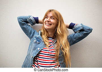 smiling young woman relaxing with hands behind head against white wall