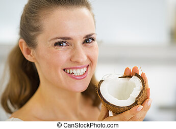 Portrait of smiling young woman showing coconut