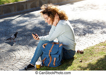 smiling young woman sitting in park looking at cellphone