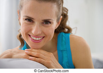 Portrait of smiling young woman sitting on couch in living room