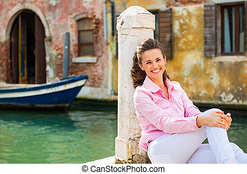 Portrait of smiling young woman sitting on street in venice, ita