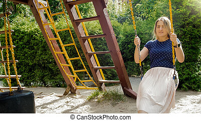 Portrait of smiling young woman sitting on swing at childs playground