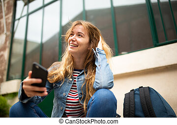 smiling young woman sitting outside with cellphone