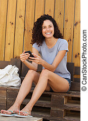 smiling young woman sitting with mobile phone