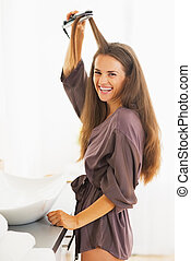 Portrait of smiling young woman straightening hair with straightener