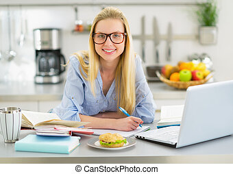 Portrait of smiling young woman studying in kitchen