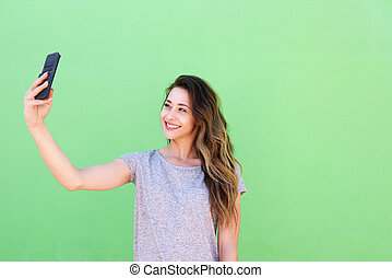smiling young woman taking selfie against green background