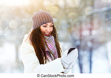 Portrait of smiling young woman talking mobile phone in winter park