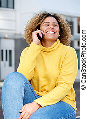 smiling young woman talking on mobile phone in city