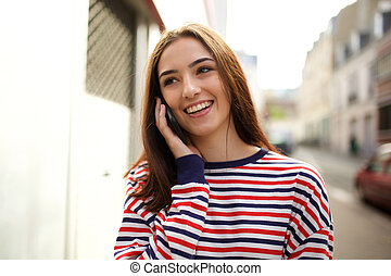 smiling young woman talking with cellphone in city