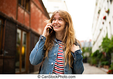 smiling young woman talking with mobile phone outside in city