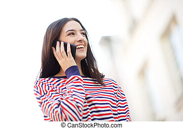 smiling young woman talking with mobile phone