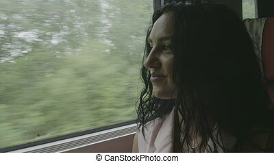 Portrait of smiling young woman traveling by train looking through the window admiring on landscape passing time