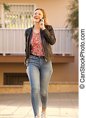 smiling young woman walking and talking on mobile phone outdoors