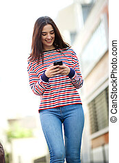 smiling young woman walking in city and looking at mobile phone
