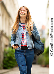 smiling young woman walking outside with mobile phone and bag