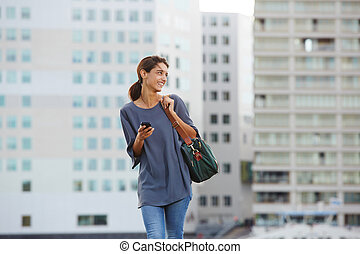 smiling young woman walking with a bag in city