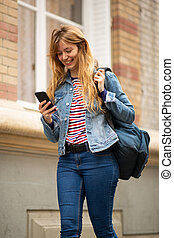 smiling young woman walking with bag and looking at mobile phone in city