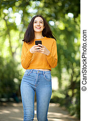 smiling young woman walking with cellphone in the park