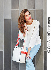 smiling young woman with a handbag looking away