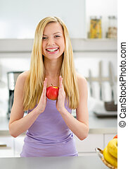 Portrait of smiling young woman with apple in kitchen